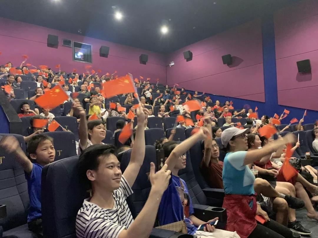 廣州某影廳,觀眾揮舞國旗等待直播開始。
