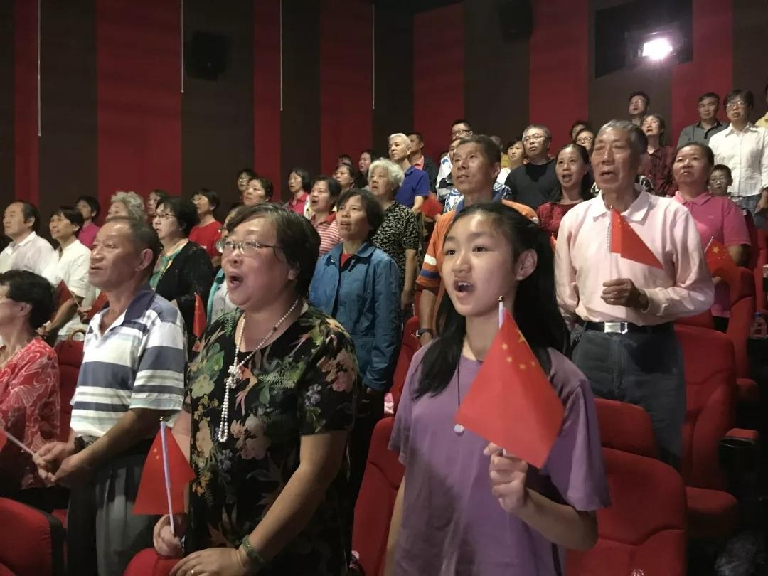 觀眾在上海某電影院觀看盛典,共唱國歌。